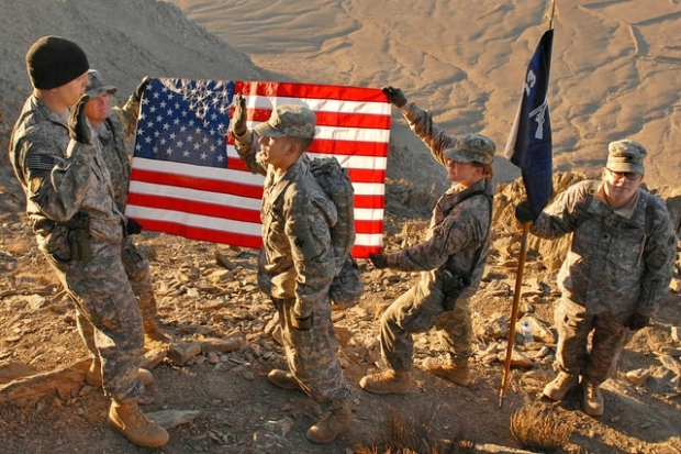 United States Soldiers holding the American Flag on top of Ghar Mountain in Afghanistan.  This was a re-enlistment ceremony.